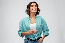 digestion, eating people concept - happy smiling full young woman in turquoise shirt touching her tummy over grey background