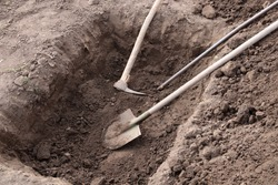 Digging a pit. Pit in the ground. The shovel, pickaxe and crowbar lay in the pit.