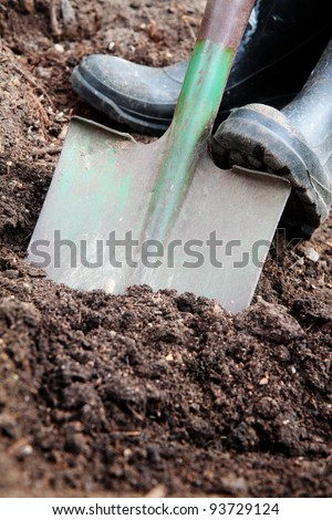 Digging soil with a spade & rubber boots.