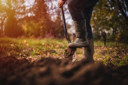 Digging the earth with a spade at countryside. Male foot wearing a rubber boot digging the earth with a spade close up.