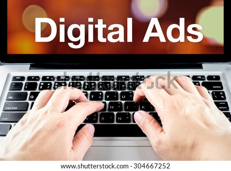 Digital ads word on laptop screen with hand type on keyboard, Digital Advertising concept.