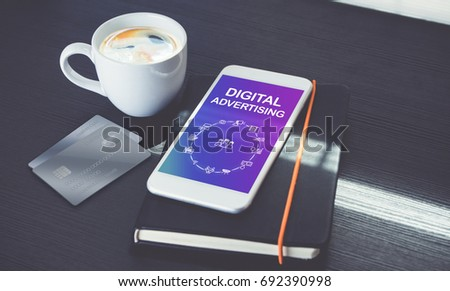 Digital advertising features icons on mobile phone screen lay on black notebook with black coffee cup near window with sunlight on black wooden desk,Digital marketing strategy business concept