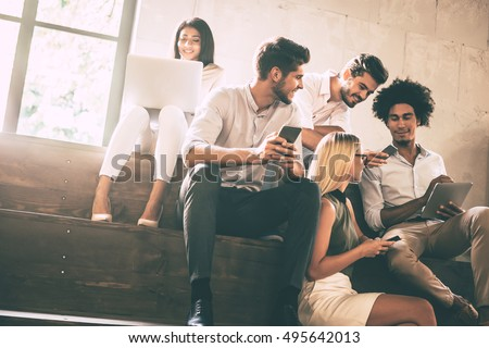 Digital age students. Group of cheerful young people communicting while holding different gadgets and sitting close to each other on steps