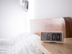 Digital alarm clock display 6 AM on the wood table next to the bed in bedroom.
