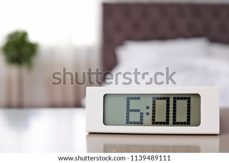Digital alarm clock on table in bedroom. Time to wake up
