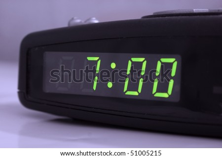 Digital alarm clock with green digits showing seven oclock