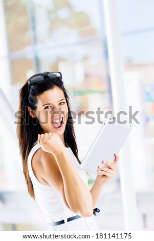 Digital business success in internet concept. Successful woman celebrating achievement with digital tablet indoor.