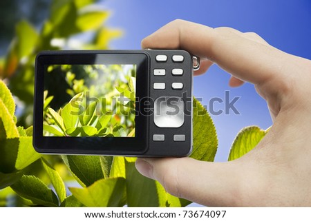 digital camera in hand on sky background