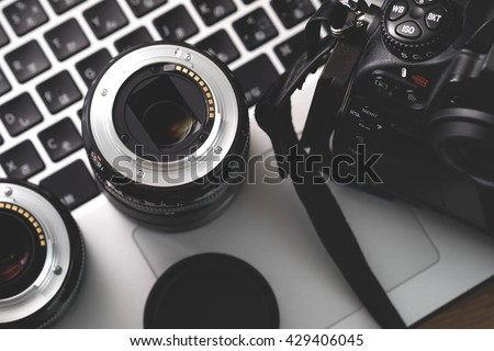 Digital camera, lens and laptop. concept of photographer work station.