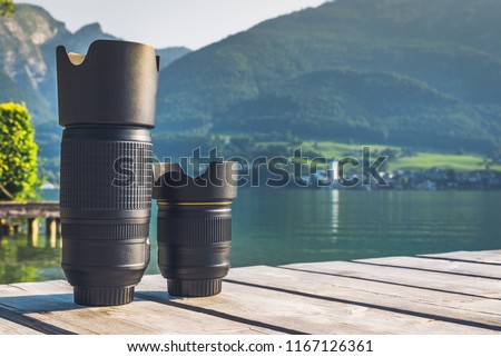 Digital camera lenses standing on wooden board with mountain landscape at background. Copy space background