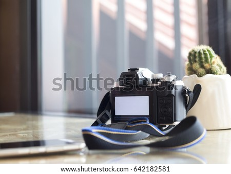 Digital camera on glass table in coffee shop.