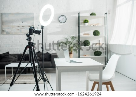 Photo of  digital camera on tripod near ring lamp and table with laptop