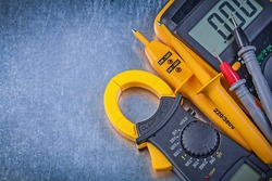 Digital clamp meter electrical tester multimeter on metallic background.