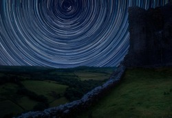 Digital composite image of star trails around Polaris with Beautiful image of medieval castle ruins in landscape with moody sky background