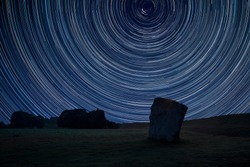 Digital composite image of star trails around Polaris with Beautiful Summer landscape of Neolithic standing stones in English countryside
