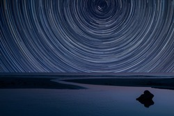 Digital composite image of star trails around Polaris with landscape of low tide beach