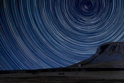 Digital composite image of star trails around Polaris with landscape of Norber Ridge and stone barn in Yorkshire Dales National Park
