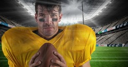 Digital composite of american football  player standing in stadium holding the ball