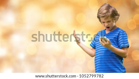 Digital composite of Angry boy holding mobile phone over blurred background #1052799782
