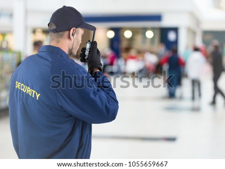 Digital composite of Back of security guard with walkie talkie against blurry shopping center