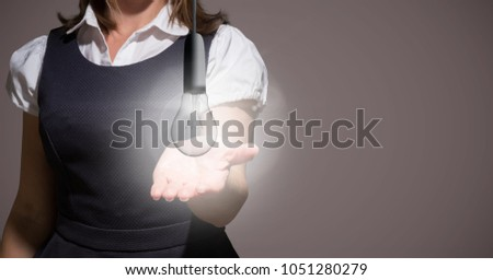 Digital composite of Business woman mid section with glowing light bulb against brown background #1051280279