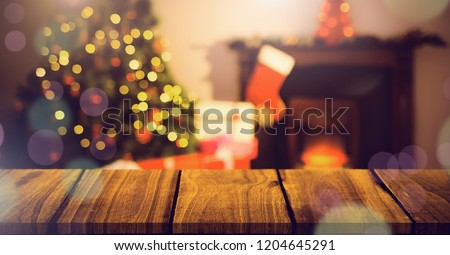Digital composite of Christmas home with tree and stocking and wooden surface with bokeh lights