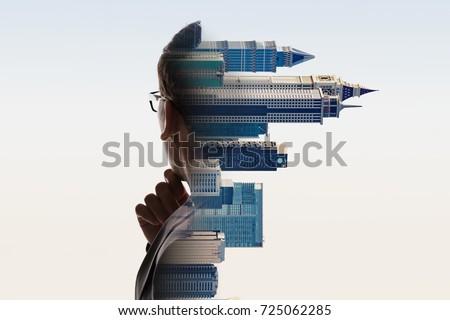 Digital Composite Of City And Contemplating Businessman Portrait