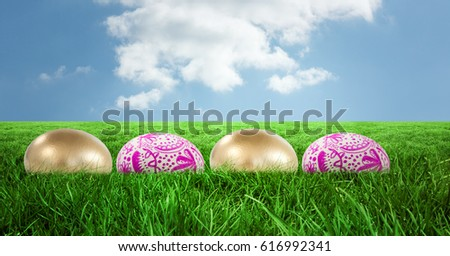 Digital composite of Easter eggs in front of blue sky #616992341