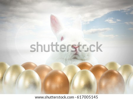 Digital composite of Easter rabbit with gold eggs in front of blue sky #617005145