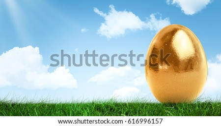 Digital composite of Gold Easter egg in front of blue sky #616996157