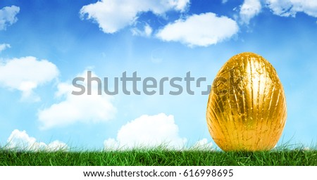 Digital composite of Gold Easter egg in front of blue sky #616998695