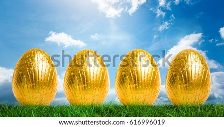 Digital composite of Gold Easter Eggs in front of blue sky #616996019