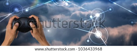 Stock Photo Digital composite of Hands playing with computer game controller with bright light connections in sky background