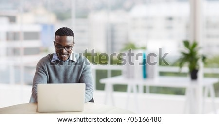 Digital composite of Happy business man at a desk using a computer