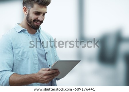 Digital composite of Happy business man using a tablet against blue blurred background #689176441