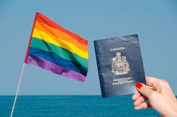 Digital composite of LGBT flag isolated overlooking the ocean with holding Canadian passport on foreground