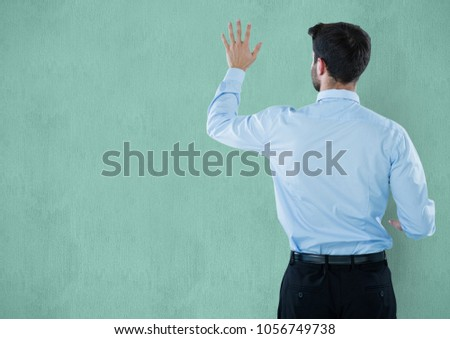 Digital composite of Rear view of businessman touching green wall #1056749738