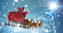 Digital composite of Santa flying in sleigh with Christmas sky