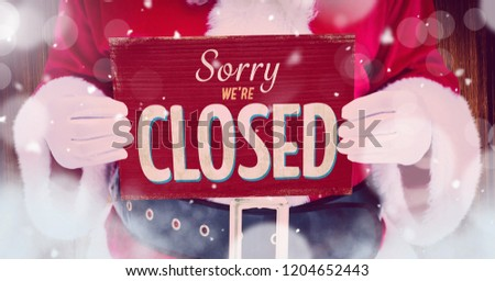 Digital composite of Sorry we're closed sign in hands of Santa with snow #1204652443