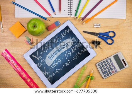 Digital composite of Tablet on a school table with school icons on screen