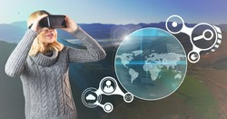 Digital composition of woman using virtual reality headset and connecting icons with landscape in background
