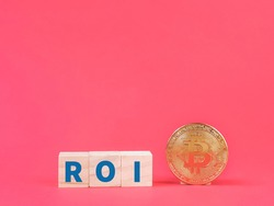 Digital currency concept. Text ROI or return in investment on wooden cubes with bitcoin against red background.