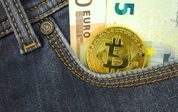 Digital currency money trading with bitcoin cryptocurrency concept, golden coin against euro money in pocket of denim jeans, close-up view photo