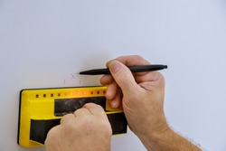 Digital detector man hand is scanning wall by sensors precision stud finder wooden beams soft focus