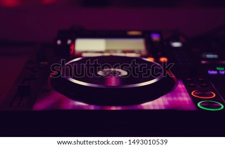 Digital dj turntable on concert stage in magenta lights.Professional disc jockey audio equipment for party.Play musical tracks and remix popular songs at festival with cd turn table setup