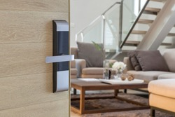 Digital Door handle or Electronics knob  for access to room security, Door wooden half opening through interior living room background, selective focus