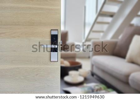 Digital door lock installed on wood door for security and access the room. Door wood texture with electronic door lock opened in front of blur living room. Selective focus.