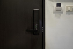 Digital door lock on modern black wooden door for protection and safety for home.