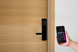 Digital door lock systems control by mobile phone for access security and protection. Man or woman user mobile for access digital door lock systems. Selective focus.