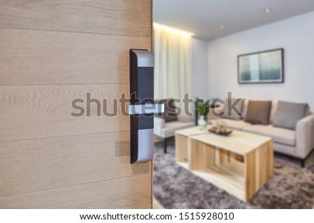 Digital door locking installed on wood door panel for security and access the room. Door wood texture with electronic door lock opened to see living room. Selective focus.